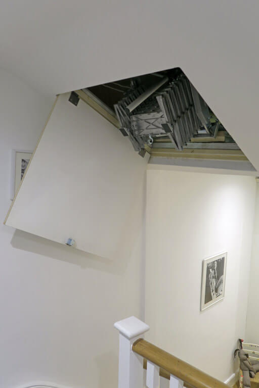 Elite loft ladder fitted behind an angled loft hatch in a sloping ceiling