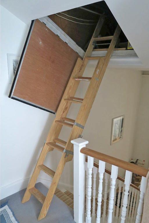 Sliding wooden loft ladder fitted into sloping loft hatch